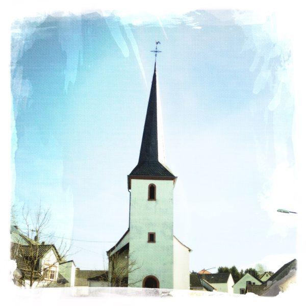 Spitzer Kirchturm, dessen Dach sich nach rechts neigt. Am unteren Bildrand erkennt man die Dächer einiger Dorfhäuser und ein paar kahle Bäume. Der Himmel ist blau.