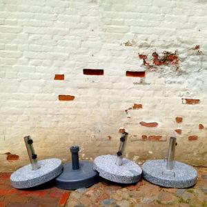Vier Sonnenschirmständer, schlicht, rund, mit kurzer Schirmfußhülse liegen unsauber teils halb aufeinander gelegt vor eine gekalkten Backsteinwand, durch deren abbröckelnde Kalkfarbe einzelne Ziegel rötlich lugen.