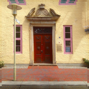 Eine verzeirte braune Tür in einer schmucken Hausfassade vor Gehweg neben Straßenlaterne. Zwei längliche hohe Fenster flankieren die Tür rechts und links. Der Gehweg besteht aus rotem Backsteinpflaster.