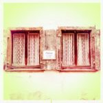 Zwei kleine alte Halbflügelfenster, dazwischen eine Plakette. Zugezogene Vorhänge. Fehlfarben von rötlich-braun bis gelb.