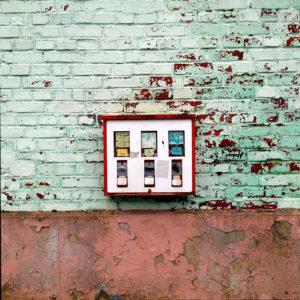 Ein uralter Kaugummiautomat mit drei Fächern hängt einer Kupferoxidgrün gepinselten Backsteinwand über eine Rosarötlich bis bräunlichen Sockel.