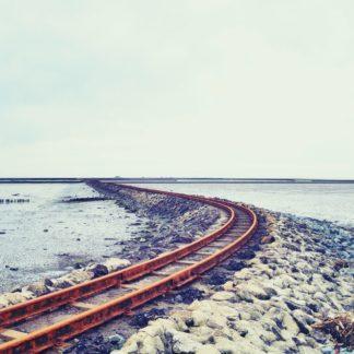 Aus der linken unteren Bildecke führt eine rostrote Bahnschiene in einem Bogen auf einem Bahndamm aus Wackersteinen in die ruhige See und verliert sich an schmalem Horizont.