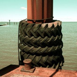 Vier alte Traktorhinterreifen umgeben einen rostogen Stahlpoller auf einem Schiffslandesteg. Dahinter das Meer und links ganz klein im Hintergrund weitere Landungsstege. Das Pfeilprofil der vier Reifen zeigt einheitlich nach links.