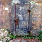Tür in einer derben Betonwand mit verrosteten Riegeln und Bändern. Grünes quillt aus den Ritzen am Fuß der Wand.