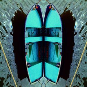 Eine bläulich verfremdete Spiegelun eines Ruderboots, senkrecht setehnd, nicht mehr an ein Boot auf dem Wasser erinnernd. Es sieht ein bisschen aus wie eine aufgeklappte Miesmuschel in türkis-blau bis grauer Färbung