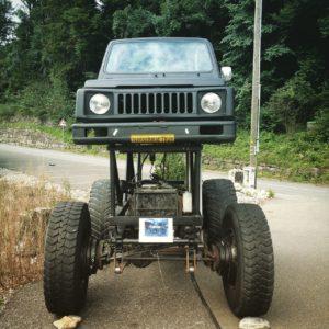 Die Karosserie eines Geländewagens älterer Bauart thront auf einem gut Schulterhohen Fahrgestell. Ansicht frontal von vorne.