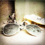 Eine schmutzige, zusammengeklappte Sonnebrille liegt in einer Ecke auf einer Betonmauer. Dahinter Papierfetzen und getrocknetes Laub.