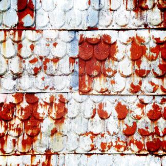 Blaugraugrünliche Metallische Verkleidung einer Hauswand in Form von Biberschwanzziegeln, nur etwas kleingliedriger. Teils ist die Farbe abgeblättert und übersättigt rostrot schimmern Placken durch.