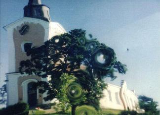 Skandinavische Kirche spiegelt sich in einem verbeulten polierten Stahl-Straßenspiegel