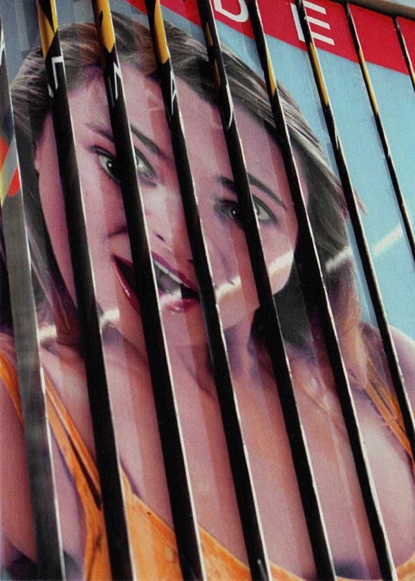 Werbeprismen einer großen französischen Werbetafels sind hängengeblieben und zeigen das Gesicht einer jungen Frau, aufgeteilt in etwa acht Lamellen.