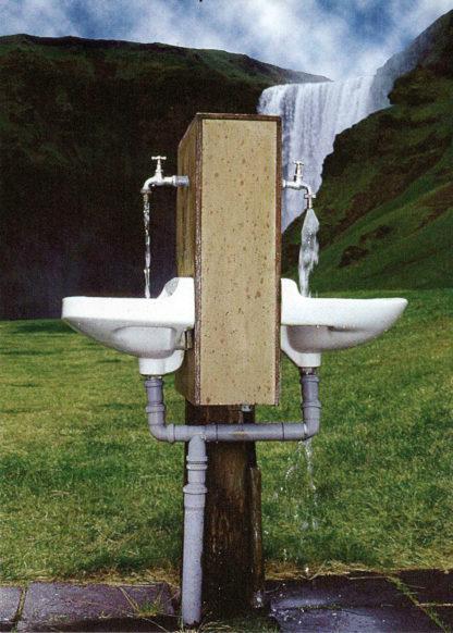 Zwei Waschbecken mit einfachen Wasserhähnen an einem Holzkasten im Freien. Im Hintergrund ein gigantischer Wasserfall. Aus den Hähnen fließt Wasser in schlichte weiße Waschbecken.