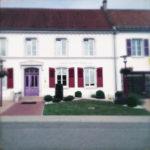 Haus an einer Dorfdurchgangsstraße. Rote Fensterläden, Steingarten, Tür
