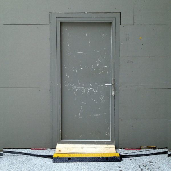 Sattgraue Tür in sattgrauer Messewand, davor ein querendes Kabel und eine gelbe Stufe