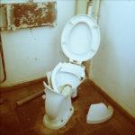 Eine geborstene, weiße Toilettenschüssel von davorstehend betrachtet. Der Deckel ist hochgeklappt. auf dem Boden liegt ein Porzellanstück. Das WC ist in einer Ecke vor alten dicken Rohren mit klassischer Druckspülung montiert.