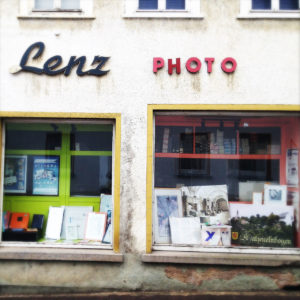 Fassade eines innerstädtsischen Fotoladens mit schöner alter Schrift Lenz PHOTO. Das H im Schriftzug wurde notdürftig repariert. Zwei Schaufenster mit gerahmten Bildern.