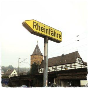 Gelbes Hinweisschild, nach links zeigend in einer Underfoot-Aufnahme in weißen Himmel ragend. Hintergrund ein runder Turm und ein Fachwerkgebäude mit weißer Mauer. Schrift auf Schild Rheinfähre.