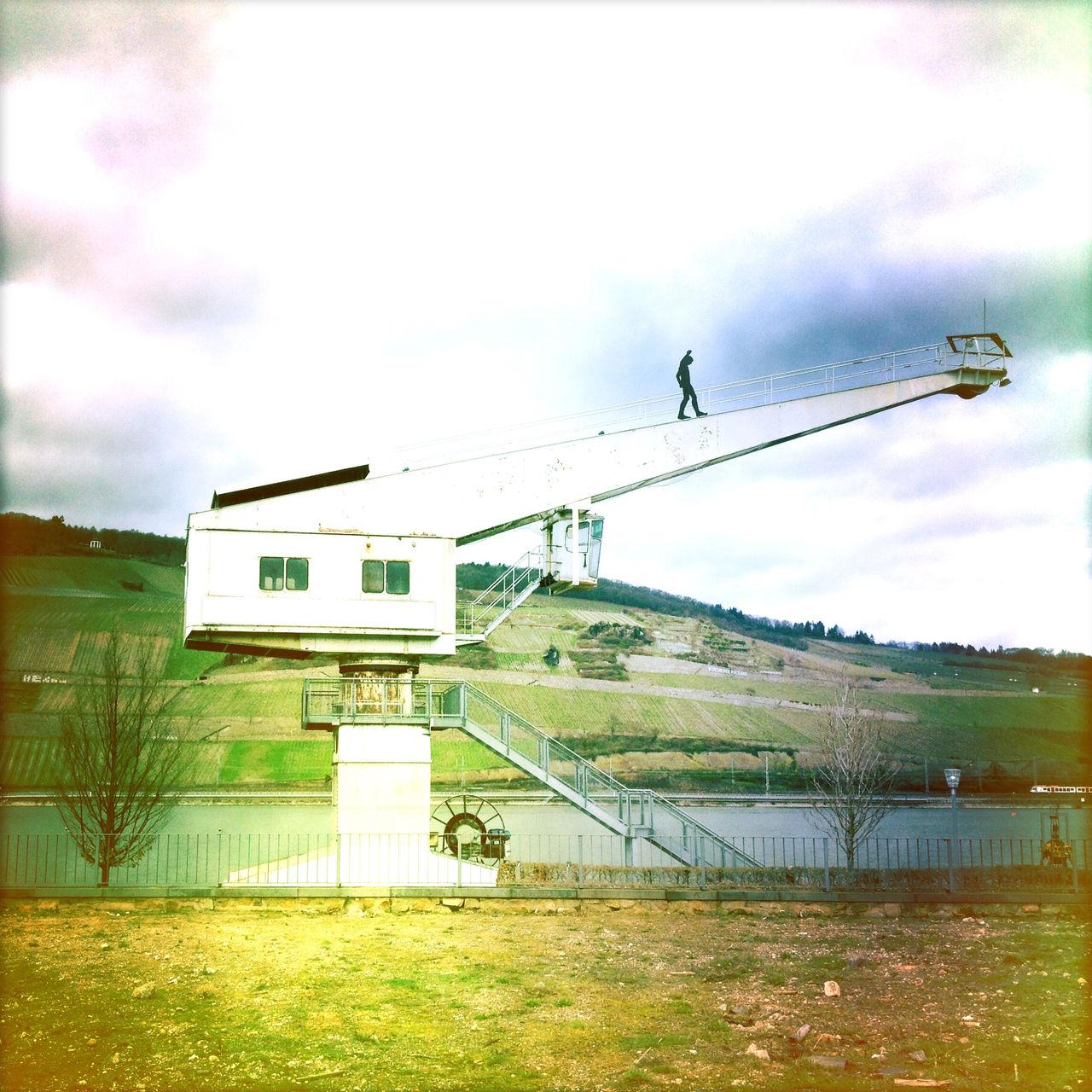Kunstwerk, Mannfigur auf dem Arm stationären Lastkrans an einem Flusshafen. Im Hintergrund Weinberge jenseits des Flusses. Fehlfarben gelb bis blaugrau.