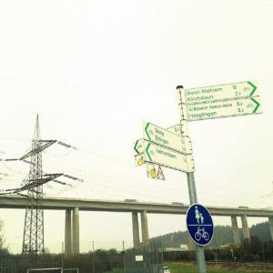 Weiße Hinweisschilder mit grüner Schrift an einem Pfosten. Radwege. Im Hintergrund eine Schnellstraßenbrücke und ein Strommast mit Hochspannungsleitung.