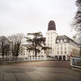 Im bräunlich gräulichen Ambiente ein altes, weißes Kurgebäude mit einem runden Turm, davor ein südländisch wirkender Nadelbaum.