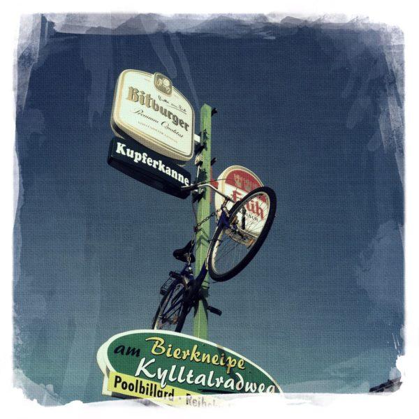 Underfootaufnahme eines Gaststättenhinweisschild, an dessen Pfosten auch ein Dekorad angebracht ist. Kupferkanne. Gaststätte am Kyllradweg.