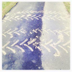 Draufsicht auf ein Stück Teerweg mit pfeilförmiger beiger Traktorspur, die den Weg quert. Ein bisschen sieht es aus wie Fischgräten. Linke obere Ecke des quadratischen Bilds zeigt ein bisschen Gras.