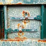 Nahaufnahme eines verriegelten Containers, dessen grüne Grundfarbe weiß überpinselt ist und sich Risse bilden. Hie und da auch ein bisschen Rost und Ringe und Riegel.