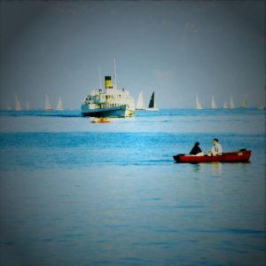 Fehlfarbenbild mit übersättigtem Blau. Rotes Ruderboot am rechten Bildrand, mittig vor Fährschiff am Horizont etwas nach links gerückt und im oberen Bilddrittel.