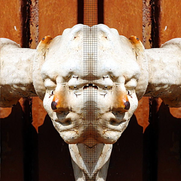 Ein zum Januskopf gespiegelter, etwas verrotteter Türknauf mit weißer, abblätternder Farbe, unter der etwas Rost gelblich rötlich an der Nasenspitze hervorlugt. Hintergrund Ockerfarben.