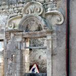 Blick durch ein reichlich verziertes Fenstergewände in einem alten hellgrauen Bauwerk. Verschnörkelter Fensterbogen, burgundisch wirkend mit vielen Schwingungen und Schlaufen. Im Fenster am unteren Bildrand lugt ein altes Achtung Baustelle-Schild und gibt mit dem roten Rand einen bunten Akzent im eigentlichen Monochrom.