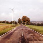 Schnurgerade Straße zwischen Wiesen. Im Hintergrund ein Windrad und einige begleitende belaubte Bäume.