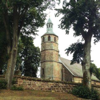 Zwischen Bäumen über einer Sandstein-Friedhofsmauer lugt ein achteckiger Kirchturm mit teilweise von den Bäumen verborgenem Kirchenschiff. Eine Art Underfoot-Aufnahme, nach oben zum Turm blickend mit stürzenden Linien.