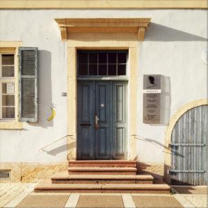 Eingangstür mit reichlich Verzierung hinter drei Treppenstufen unter Vordächlein aus Stein, das Schatten nach rechts wirft.