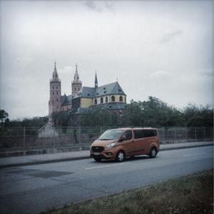 Quer über eine Straße blickend, auf der ein rötlicher Kleinbus von rechts nach Links passiert, liegt in einem Weinberg eine gotische Kirche.