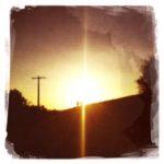 Blick von unten einen Damm aufwärts gegen die untergehende Sonne, die einen Reflex als senkrechten Strich durchs Bild zieht. Auf dem Damm laufen zwei Menschen, erkennbar nur als winzige Silhouette neben einem großen Telegrafenmast.