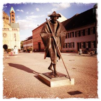Lebensgroße Bronzestatue eines Pilgers mit Mantel, Hut, auf einen mannshohen Stab gestützt gehend. Im Hintergrund angeschnitten ein Kirchturm (des Speyrer Doms).