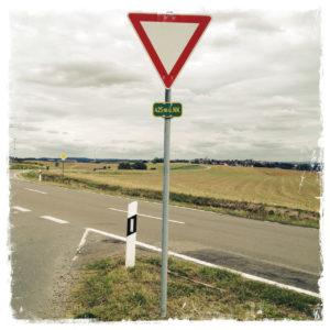 Mittig im Bild ein Vorfahrt beachten Schild, an dessen Pfosten ein Höhenangabenschild befestigt ist. Straßengabelung zwischen kahlen Feldern.