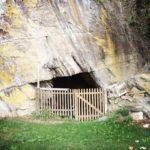 Gatter vor einer Felsenhöhle. Im Vordergrund eine grüne Wiese.