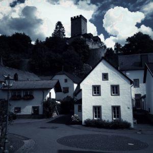 Düsteres dunkelgrau-blaues Bild. Einfamilienhaus älterer Bauart in Hell unter der Silhouette einer Burg und bedrohlich wirkendem Himmel mit dicken hellen Quellwolken.