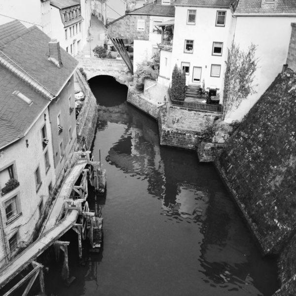 Blick abwärts auf einen schmalen Mühlbach innerorts, der zwischen hohen Mauern vorbei an einer alten Mühle fließt.