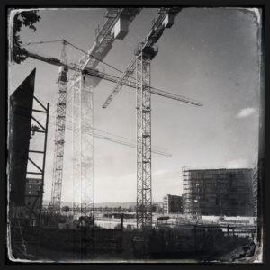 Baukräne auf offenem Gebiet. Retrobild in schwarzweiß. Es sind noch kaum Mauern hochgezogen. Viel Himmel, wolkenlos.