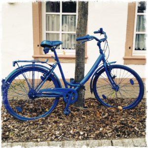Blau gestrichenes Fahrrad, auf Ständer stehend vor einem dünnen Baumstamm vor einer Hausfassade mit Buntsandsteingewändeten Fenstern.