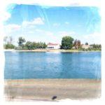 Wie eine Trikolore wirkt die entfremdete Landschaftsaufnahme, von Ufer zu Ufer blickend an einem Türkisblauen Fluss. der Untere Colorstreifen ist teergrau, der mittlere, der Fluss, türkisblau, gefolgt vom oberen Color, einem von blassen Wolkengefielden durchwirkten Himmel, gebrochen nur von einem schmalen Streifen Land auf der gegenüberliegenden Flussseite. Belaubte Bäume umschmiegen in diesem Bereich einen Fähranleger mit Haus.