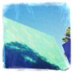 Blaue Hausfassade mit Schatten eines Baumes unter Himmel. Das Bild besteht aus verschiedenen bläulich gefärbten Flächen