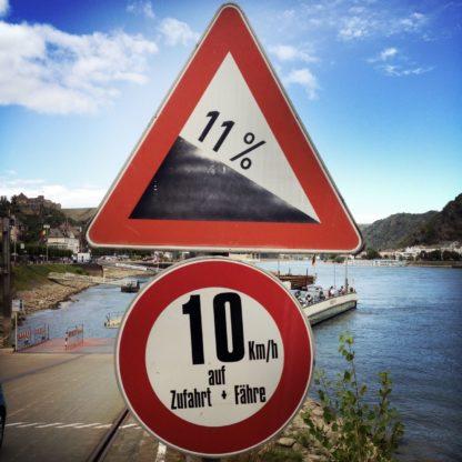 Dominant bildfüllendes Warnschild 11% Gefälle Symbol über rundem Verbotsschild 10 km. Im Hintergrund ein Fähranleger und angedeutet hinter dem Schild die anlegende Fähre.