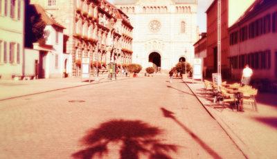 Rötlich fehlfarbiges Straßenbild zwischen Bischhöflichen großen Stadtbauten, die den Blick auf einen Dom lenken. Der Schatten einer jungen Palme fällt im Vordergrund bis fast zur Bildmitte