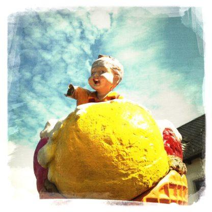 Underfootaufnahme eines übergroßen gelben Eisbällchens, auf dem eine Kinderfigur die abe Hand gen Himmel reckt.