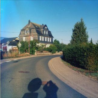 Straßenflucht auf ein großes einzelstehendes Haus mit Walmdach unter blauem Himmel. Am Rand Hecken und ein Baum. Der Schatten des Fotografen fällt neben dem Schatten eines runden Verkehrsschilds auf die Straße.
