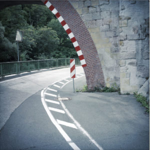 Eine bogenförmige Durchfahrt unter einer Eisenbahnbrücke ist mit rot-weißen Markern versehen. Gegen eine Straßenmarkierung bilden sich zwei harmonierende Bögen, die das Bild markant dominieren.