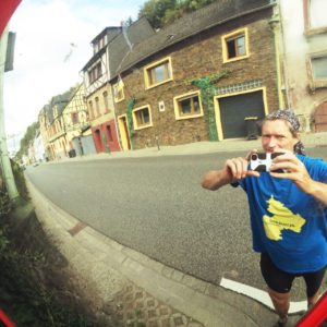Handyfotografierender Mensch mit blauem T-Shirt spiegelt sich in einem innerörtlichen Straßenspiegel vor geschlossener Häuserzeile am Straßenrand. Auf dem T-Shirt ist ein gelber Umriss, der Silhouette des Bundeslands Rheinland-Pfalz, spiegelverkehrt.