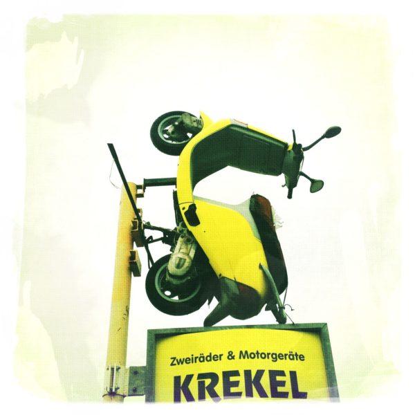 Gelber Motorroller, der senkrecht auf einem hoch in die Luft ragenden Firmenschild montiert ist und in den weißen Himmel ragt. Firmenname auf dem Schil lautet Krekel.